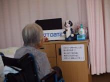 見守りサービスのロボットと会話する施設入居者