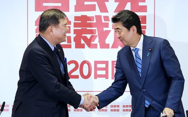 共同記者会見で質問に答える安倍首相と石破元幹事長(10日、自民党本部)