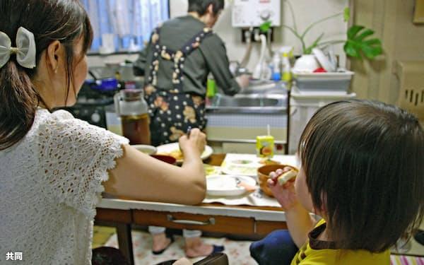 「おうち食堂」を利用し、ボランティア(奥)が作った夕食を食べる女性と長男(東京都江戸川区)=共同