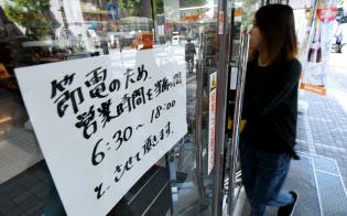 節電による営業時間短縮を伝える案内が張られたコンビニ(11日、札幌市中央区)