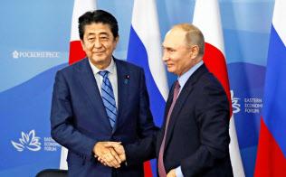 中国のネットでは安倍首相の外交を絶賛するコメントが多数みられる(10日、ウラジオストクでロシアのプーチン大統領と握手する安倍首相)=共同