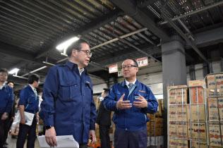 セコマの丸谷社長(右)から物流センターで説明を受ける世耕経産相(11日、札幌市)