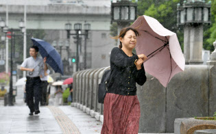強い風を受けながら、傘を差して歩く人たち(4日、大阪市中央区)