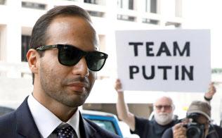 7日、ロシア介入疑惑への抗議のプラカードが掲げられる中、ワシントンの連邦地裁に到着したパパドポロス氏=ロイター