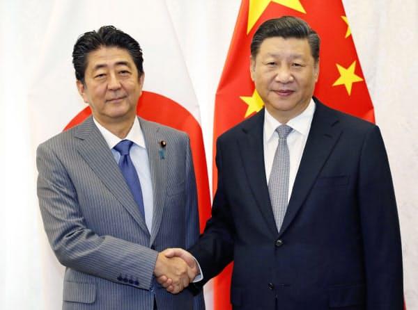 12日、会談で握手する中国の習近平国家主席(右)と安倍首相(ロシア・ウラジオストク)=共同