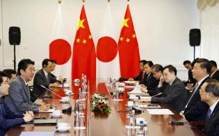 12日、ロシアのウラジオストクで会談する中国の習近平国家主席(右手前から2人目)と安倍首相(左手前から2人目)=共同
