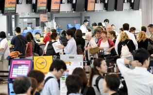 一部再開した第1ターミナルの国際線出発ロビーで搭乗手続きのため並ぶ人たち(14日午前、関西空港)