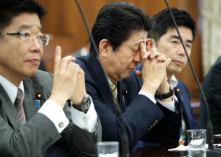 参院厚労委に出席し疲れた表情を見せる安倍首相。左は加藤厚労相(6月)