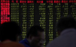 北京の証券会社で株価ボードを見つめる投資家たち(17日)=AP