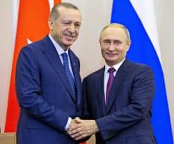 会談後の共同記者会見で握手するロシアのプーチン大統領(右)とトルコのエルドアン大統領(17日、ソチ)=AP