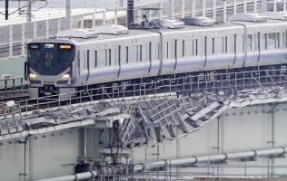 運転を再開し、タンカー衝突の爪痕が残る関西空港連絡橋を走るJRの始発列車(18日)=共同