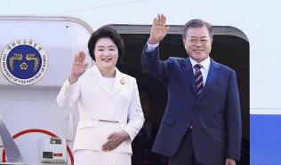 平壌へ向かう専用機に乗り込む前に、見送りの人に手を振る韓国の文在寅大統領夫妻(18日、ソウル近郊)=聯合・共同