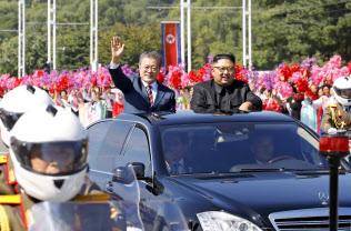 18日、平壌の沿道を埋めた市民に手を振って応える韓国の文在寅大統領(左)=平壌写真共同取材団撮影