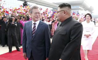 平壌の空港で、出迎えた北朝鮮の金正恩委員長(手前右)と並んで歩く韓国の文在寅大統領(同左)=18日、平壌写真共同取材団撮影
