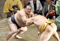 18日、稀勢の里(左)は遠藤を寄り切りで下し、勝ち越しを決めた=共同