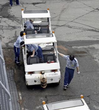 浸水被害を受けた車両を動かす作業員ら(10日、関西国際空港)=共同