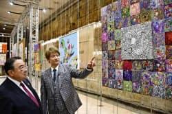 18日、パリで開かれた展覧会の内覧会で木寺昌人駐フランス大使(左)に作品を説明する香取慎吾さん=共同