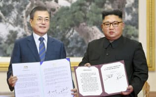 平壌で首脳会談後、署名した「9月平壌共同宣言」を見せる韓国の文在寅大統領(左)と北朝鮮の金正恩委員長=19日、平壌写真共同取材団撮影