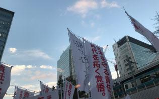 19日、JR秋葉原駅前の演説会場では支持と批判ののぼりが交錯した