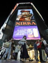 北海道電力苫東厚真発電所の1号機が再稼働し、点灯された歓楽街・ススキノの「ニッカウヰスキー」の看板(19日夕、札幌市)=共同