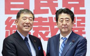 共同記者会見を前に握手する安倍首相と石破元幹事長(10日、党本部)