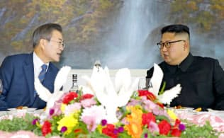 昼食会で言葉を交わす文大統領と金委員長(19日、平壌の冷麺店)=平壌写真共同取材団撮影