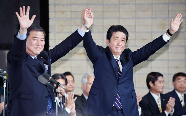 自民党総裁に選出され石破氏と手を取り合う安倍首相(20日午後、党本部)