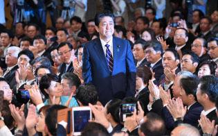 自民党総裁に選出され起立する安倍首相(20日、党本部)