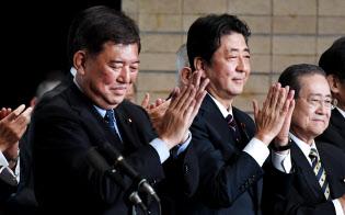 総裁選を終え拍手する石破氏(左)と安倍首相(20日、自民党本部)