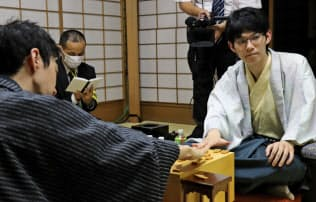 将棋王座戦第2局を制した斎藤七段。左は中村王座(20日午後、京都市)