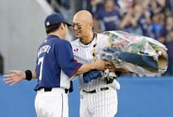 8回、通算2千安打を達成し、西武・松井(左)から花束を受け取るロッテ・福浦(22日、ZOZOマリン)=共同