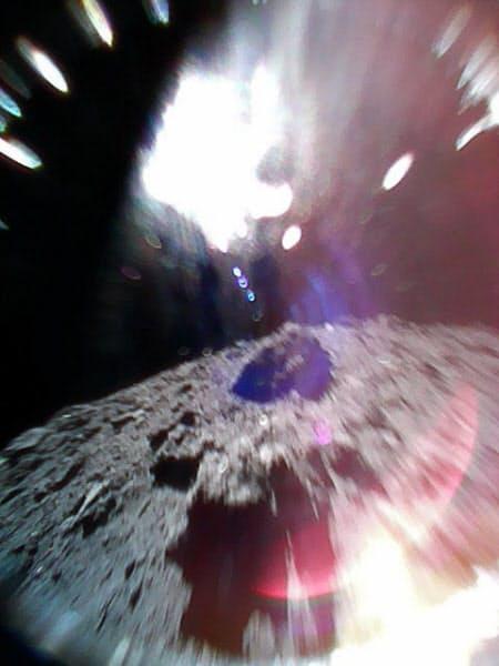 着陸に成功した探査ロボットが跳びはねながら移動した際に撮影した写真(下がりゅうぐうの地表、上は太陽光の影響)=JAXA提供