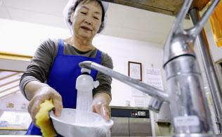 北海道厚真町の介護施設で食器を洗う調理スタッフ(21日)=共同