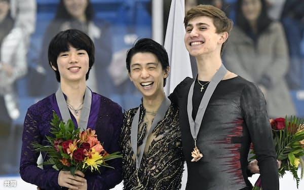 金メダルを獲得し表彰式で笑顔の羽生結弦(中央)。左は2位の車俊煥(22日、オークビル)=共同