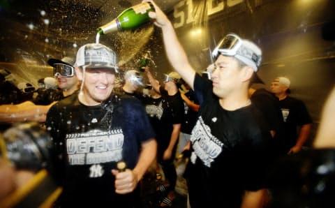22日、プレーオフ進出が決まり、シャンパンファイトを楽しむ田中(右)=AP