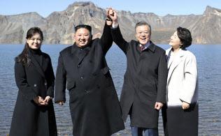 朝鮮半島最高峰の白頭山を訪問し、カルデラ湖「天池」でつないだ手を上げる北朝鮮の金正恩朝鮮労働党委員長(中央左)と韓国の文在寅大統領(同右)。夫人が同行した(20日)=平壌写真共同取材団撮影