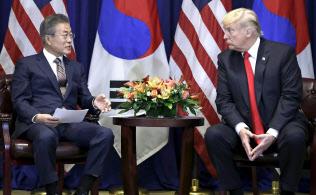 韓国の文在寅大統領の話を聞くトランプ米大統領(右)=24日、ニューヨーク(AP)