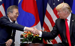 米韓首脳会談で握手するトランプ米大統領(右)と文在寅韓国大統領(24日、ニューヨーク)=ロイター