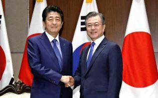 25日、ニューヨークでの会談前に韓国の文在寅大統領(右)と握手する安倍首相=共同