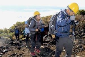 御嶽山噴火から4年を前に、山頂を目指して慰霊登山をする遺族ら(26日、長野県木曽町)=共同