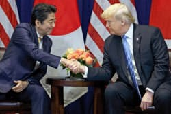 26日、ニューヨークで日米首脳会談を前に握手するトランプ米大統領(右)と安倍首相=AP