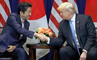 26日、ニューヨークで首脳会談を前に握手するトランプ米大統領(右)と安倍首相=AP