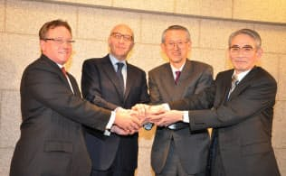 日本での証券会社統合を発表した記者会見で手を携えるモルガンと三菱UFJの首脳ら(2009年3月、都内)
