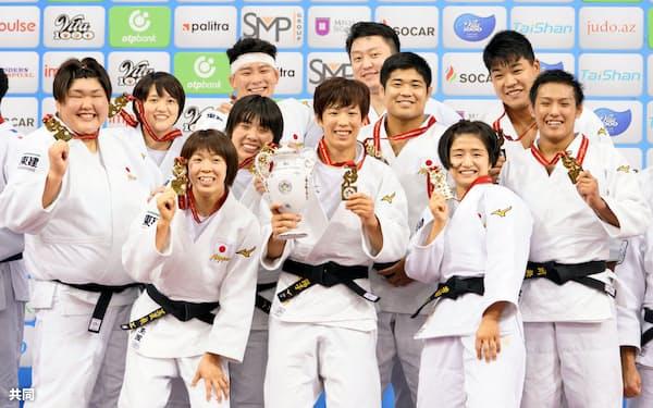 柔道の世界選手権、男女混合団体で2連覇し、表彰式で金メダルを手に笑顔の大野陽子(中央)ら日本選手(27日、バクー)=共同