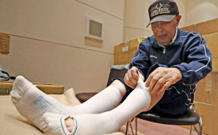 避難所で医療用弾性ストッキングをはく男性(26日、北海道安平町)=共同