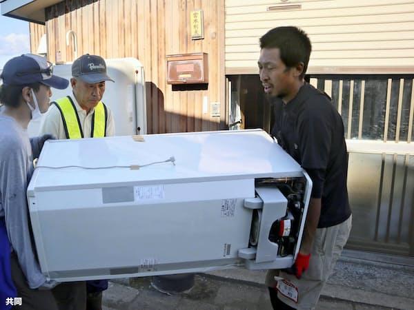 台風の接近を警戒し、北海道地震の被災者の自宅前でごみとなった冷蔵庫を運び出すボランティアら(29日、北海道安平町)=共同