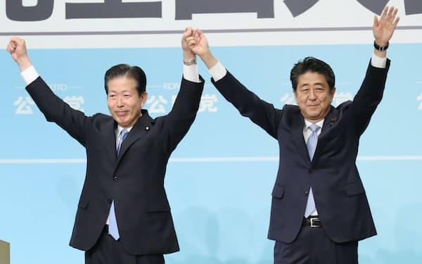 公明党全国大会で6選を承認された山口代表(左)と手を取り合う安倍首相(30日午後、東京都千代田区)