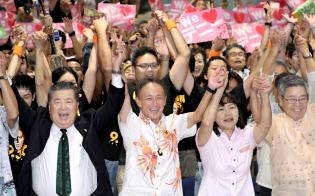 当選を確実にし万歳する玉城デニー氏(30日、那覇市)=塩山賢撮影