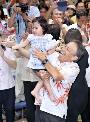 子供を抱き上げて喜ぶ玉城デニー氏(30日、那覇市)