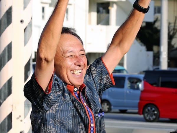 沖縄県知事選から一夜明け、街頭で手を振る玉城デニー氏(1日午前、沖縄県沖縄市)